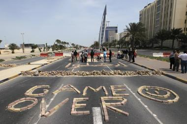 "Anti-government protesters form the words ""Game Over"" with bricks as they block the roads from riot police at the junction of Bahrain Financial Harbour in Manama"