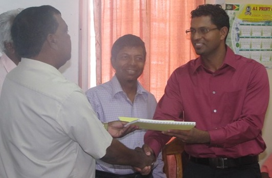 Pulandar Khandi and the supplier of the equipment, Krishendat Sukhu of Digital Technology shake hands