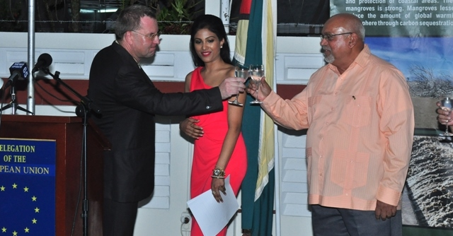 Donald Ramotar and EU Head of Delegation to Guyana, Ambassador Robert Kopecky toast on the occasion of Europe Day. Miss India Worldwide 2012 Alana Seebarran looks on